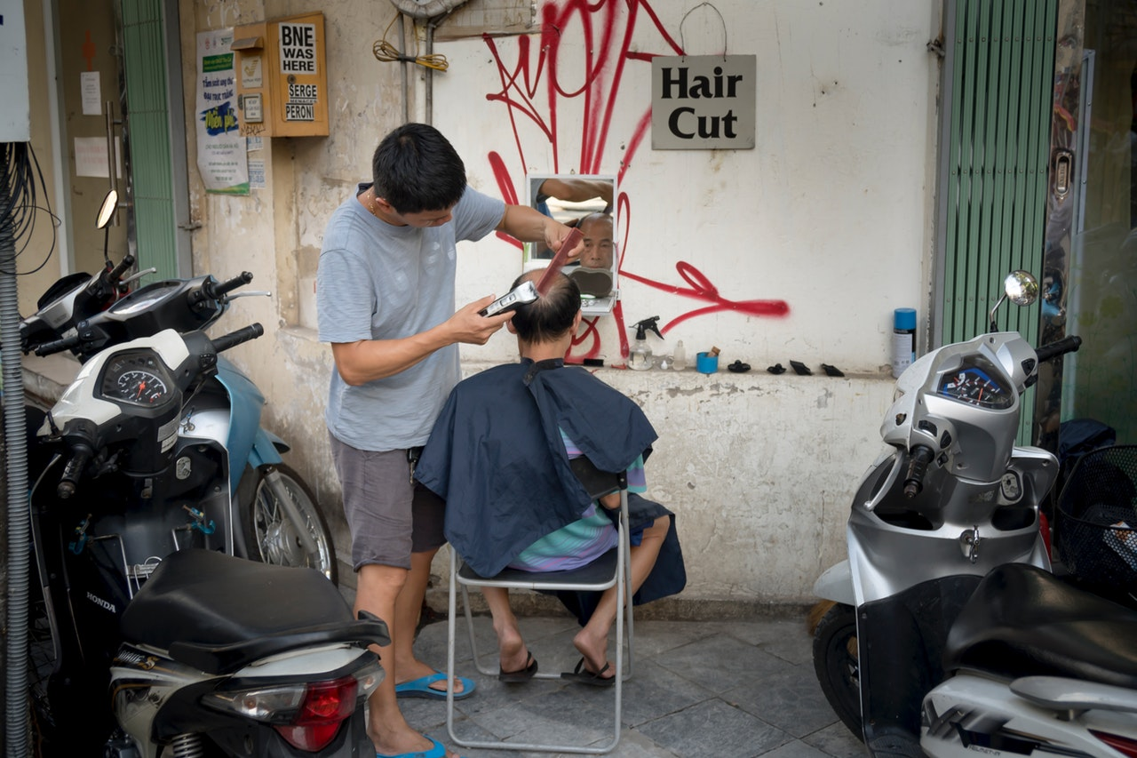 a man cutting the hair of another